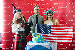 Alan Cumming and piper Louise Marshall, with the cake, as Delta launching year-round nonstop service from Edinburgh to New York-JFK today at Edinburgh Airport.