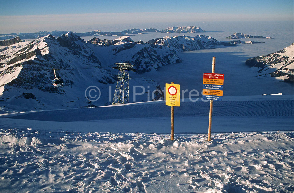 A warning sign on an alpine mountaintop for skiers, tells them of a closed piste and of a no marked and controlled trail. From the heights of this Alpine mountain, we look down the snow-filled valleys on a beautifully clear winter's day. Lower peaks stretch into the distance and it is a landscape of extreme beauty and wonder. Little pollution or smog is evident and we see the sign that is situated in plain view of skiers who have dismounted their cable car in Liechtenstein. The warnings are written in 4 languages: German; French; Italian and English for the sake of international skiing enthusiasts who may wish to venture off-piste, taking their own risks but enjoying as much more adventurous form of free skiing.
