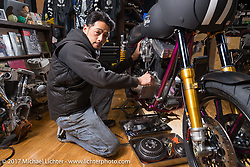 Yutaka Nishida wrenching on a custom in his Joyride Speed Shop. Kodaira City, Tokyo, Japan. Friday December 8, 2017. Photography ©2017 Michael Lichter.