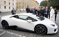 NO FRANCE - NO SWITZERLAND: November 15, 2017 : Pope Francis speaks with CEO of Lamborghini Stefano Domenicali next to a white Lamborghini donated to the pontiff by the luxury sports car maker, at the Vatican.