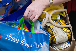 Woman carrying her shopping in reusable 'bags for life' shopping bags,