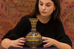 "© Licensed to London News Pictures. 23/10/2020. LONDON, UK. A staff member presents ""A Highly Important Mamluk Gilded And Enamelled Glass Flask"", Syria, Mid-13th Century, (Estimate GBP300,000-500,000), at Sotheby's, New Bond Street during the preview of their auction of Treasures from the Islamic World on October 27.  Photo credit: Stephen Chung/LNP"