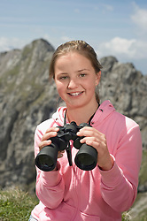 Young teenage girl holding binoculars in Alps