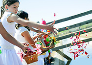 Robin Zielinski – Sun-NewsLas Cruces Catholic School student McKree Riley, 9, tosses flower petals into the water with others on Thursday at the New Mexico Farm & Ranch Heritage Museum during the 16th annual Blessing of the Fields.