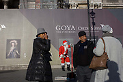 A busker dressed as Santa with visitors to Trafalgar Square, central London. Seemingly sitting in the frame of a portrait by the Spanish artist Goya, we see visitors looking around for directions in this landmark in the middle of the capital. It is weeks before Christmas and on tghe left we see the Countess-Duchess of Benavente by Francesco Goya (1885), work sponsored by Credit Suisse and advertised on a construction hoarding outside the National Portrait Gallery. Doña María Josefa Alonso-Pimentel y Téllez-Girón, Duchess of Osuna, Grandee of Spain, suo jure 15th Countess-12th Duchess of Benavente, Grandee of Spain (1752 - 1834) was a Spanish aristocrat, famous for her patronage of artists, writers and scientists and who died at the age of 81.