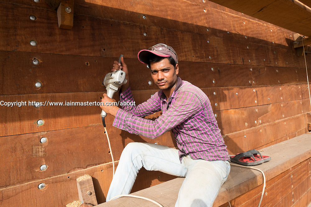 Portrait of worker building a traditional wooden dhow cargo ship in shipyard beside The Creek River in Dubai United Arab Emirates