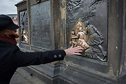 A tourists hand reaches out to touch and help polish part of the statue of St John Nepomuk on Charles Bridge,  on 18th March, 2018, in Prague, the Czech Republic.