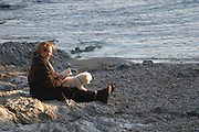 Woman sitting by White cliffs on the St Pierre des Embies island outside Sanary with dark blue sea and sky at late afternoon sunshine Le Brusc Six Fours Var Cote d'Azur France