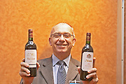 Alain Brumont, owner and winemaker at Chateau Montus and Domaine de Bouscasse Bouscassé holding a bottle of each wine. Madiran, France Madiran France