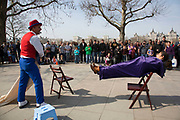 Street performer performs a levitation trick with a member of the public from the gathered crowd. Balanced on two chairs, one is removed. The South Bank is a significant arts and entertainment district, and home to an endless list of activities for Londoners, visitors and tourists alike.