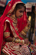 A young girl wearing a traditional bridal outfit at the Desert Festival on 29th January in Jaisalmer, Rajasthan, India. It is an annual event that take place in February month in the beautiful city Jaisalmer. The bridal dowry is a rich aray of silver and gold jewelry and the hands and arms are adorned with henna patterns.