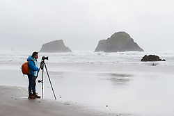 Photographer at Crescent Beach, Ecola State Park, Oregon, USA.