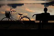 Silhoutte of a Vietnamese woman sitting on a bench facing Giang Vo lake at sunset, with her bicycle parked beside, Hanoi, Vietnam, Southeast Asia