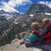 Younsters sit on a granite dome below Palisade Glacier and the eastern crest of California's Sierra Nevada in John Muir Wilderness