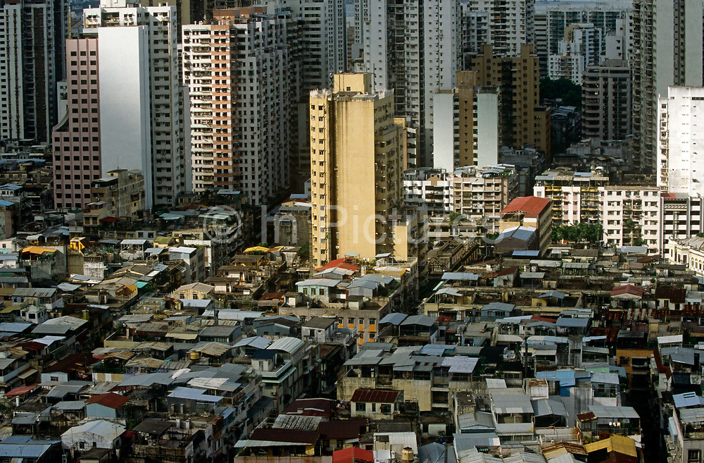 An aerial view of central Macau, looking down on high-rise apartments and poorer housing in this ex-Portuguese colony. Macau is now administered by China as a Special Economic Region (SER). Taken from a tall apartment block that overloooks the Rua do Almirant e Costa Cabral, we can view the tightly-packed cities of one of the most densely-populated conurbations in the world, this area is a packed warren of houses, businesses and tower blocks, home to a population of mainland 95% Chinese, primarily Cantonese, Fujianese as well as some Hakka, Shanghainese and overseas Chinese immigrants from Southeast Asia and elsewhere. The remainder are of Portuguese or mixed Chinese-Portuguese ancestry, the so-called Macanese, as well as several thousand Filipino and Thai nationals. The official languages are Portuguese and Chinese.