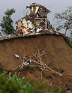 1/27/ 99 AL DIAZ/HERALD STAFF--Victims search through the debris of what remains of this home after collapsing off the face of this ridge in Armenia struck hard by Monday's earthquake Colombia.