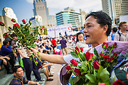 01 MARCH 2013 - BANGKOK, THAILAND: . A man sells flowers to people who want to throw them to the stage to honor Pheu Thai politicians at the last Pheu Thai campaign rally for the Bangkok Governor's election. The election is Sunday, March 3 and no campaigning is allowed 24 hours before election day. Police General Pongsapat Pongcharoen (retired), a former deputy national police chief who also served as secretary-general of the Narcotics Control Board is the Pheu Thai Party candidate in the upcoming Bangkok governor's election. He resigned from the police force to run for Governor. Former Prime Minister Thaksin Shinawatra reportedly personally recruited Pongsapat. Most of Thailand's reputable polls have reported that Pongsapat is leading in the race and likely to defeat Sukhumbhand Paribatra, the Thai Democrats' candidate and incumbent. The loss of Bangkok would be a serious blow to the Democrats, whose national base has been the Bangkok area.    PHOTO BY JACK KURTZ