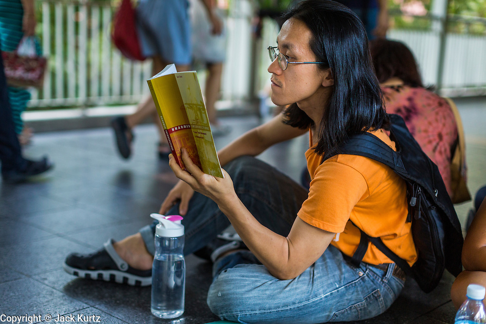 """31 MAY 2014 - BANGKOK, THAILAND: People walk by a man sitting in the Skywalk between the BTS Skytrain Siam and Chit Lom stations to silently read George Orwell's """"1984"""" and other books about civil disobedience and nonviolent protest. The protests are based on the """"Standing Man"""" protests that started in Turkey last summer. Authorities made no effort to stop the protest or interfere with the people who were reading. Bangkok was mostly quiet Saturday. There were only a few isolated protests against the coup and military government.    PHOTO BY JACK KURTZ"""