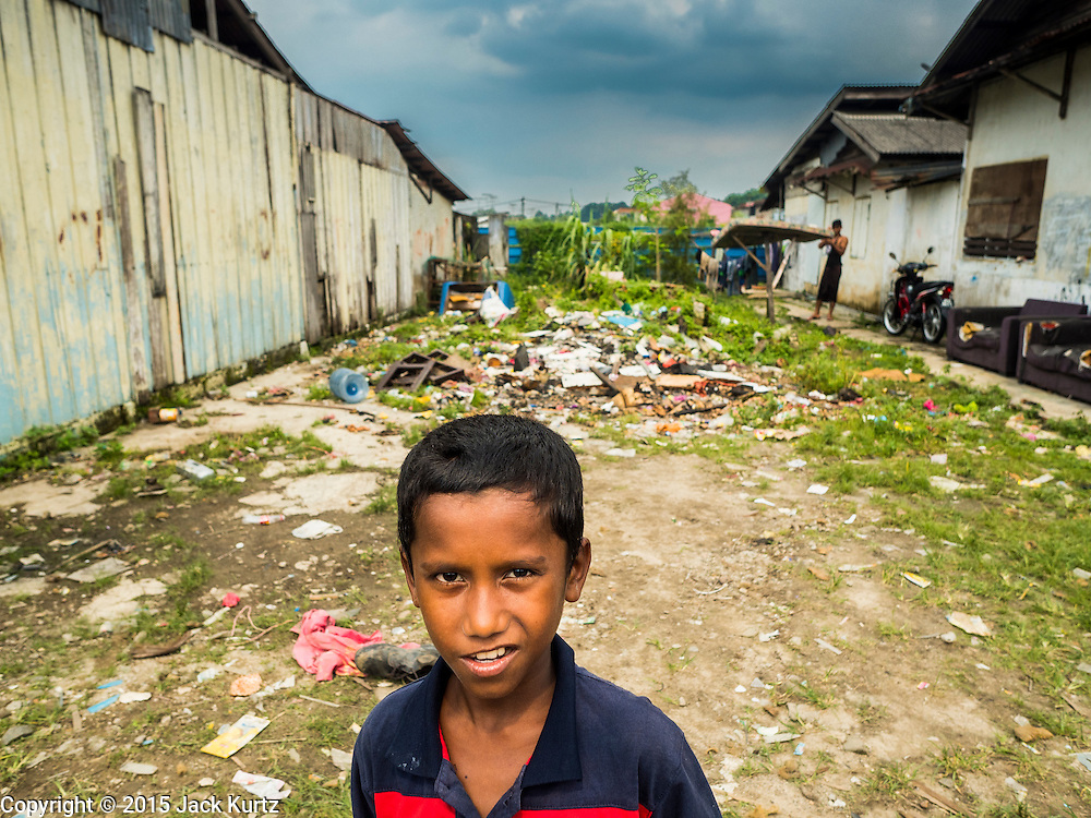 01 JUNE 2015 - KULAI, JOHORE, MALAYSIA:  A Rohingya refugee boy in front of the empty lot the Rohingya use as a playground in Kulai, Malaysia. The UN says the Rohingya, a Muslim minority in western Myanmar, are the most persecuted ethnic minority in the world. The government of Myanmar insists the Rohingya are illegal immigrants from Bangladesh and has refused to grant them citizenship. Most of the Rohingya in Myanmar have been confined to Internal Displaced Persons camp in Rakhine state, bordering Bangladesh. Thousands of Rohingya have fled Myanmar and settled in Malaysia. Most fled on small fishing trawlers. There are about 1,500 Rohingya in the town of Kulai, in the Malaysian state of Johore. Only about 500 of them have been granted official refugee status by the UN High Commissioner for Refugees. The rest live under the radar, relying on gifts from their community and taking menial jobs to make ends meet. They face harassment from Malaysian police who, the Rohingya say, extort bribes from them.       PHOTO BY JACK KURTZ