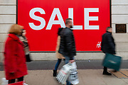 People with shopping bags walk past a sale sign in Oxford Street, London, UK on January 03, 2019