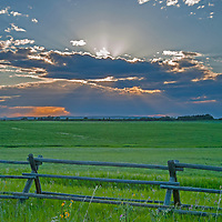 The sun sets behind a thunderstorm rain squall over the Gallatin Valley near Bozeman, Montana.  In the foreground are hay pastures and a jack leg fence, common in this area.
