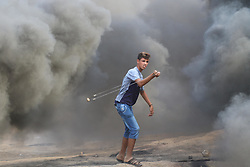 October 5, 2018 - Al-Buraj Refugee Camp, Gaza Strip - Palestinian protesters set fire to tires and throw rocks, while Israeli forces opened live fire and tear-gas bombs east of Al-Buraj refugee camp in central of the Gaza Strip, Two Palestinians killed and dozens wounded during clashes between Palestinians and Israeli troops. (Credit Image: © Hassan Jedi/Quds Net News via ZUMA Wire)