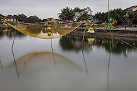 Vietnamese Fishing Net Suspended on Thu Bon River in Hoi An.  A large, empty fish net is suspended from poles over water in the harbor at Hoi An.<br /> These nets are kept this way during parts of the day to keep them untangled and to allow boats to pass by safely. They are then lowered into the water to catch fish at night or when conditions are optimal.