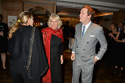 Left to right, LAURA LOPES, The DUCHESS OF CORNWALL and her son TOM PARKER BOWLES at a party hosted by Ewan Venters CEO of Fortnum & Mason to celebrate the launch of The Cook Book by Tom Parker Bowles held at Fortnum & Mason, 181 Piccadilly, London on 18th October 2016.