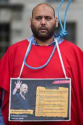 London, UK. 3rd July, 2021. A man with a noose round his neck attends a protest by anti-coup activists opposite Downing Street against political executions in Egypt on the 8th anniversary of the Egyptian military coup against President Mohamed Morsi. 92 political prisoners have been executed in Egypt since the coup, with death sentences ratified by General Abdel Fattah el-Sisi for a further 64.