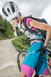 Mountainbiker with pain in bottom, Kampenwand, Bavaria, Germany