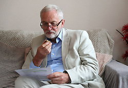 Labour leader Jeremy Corbyn looks at fuel bills as he speaks to Carol Woolford (not pictured) about fuel poverty, at her home in Reading West.