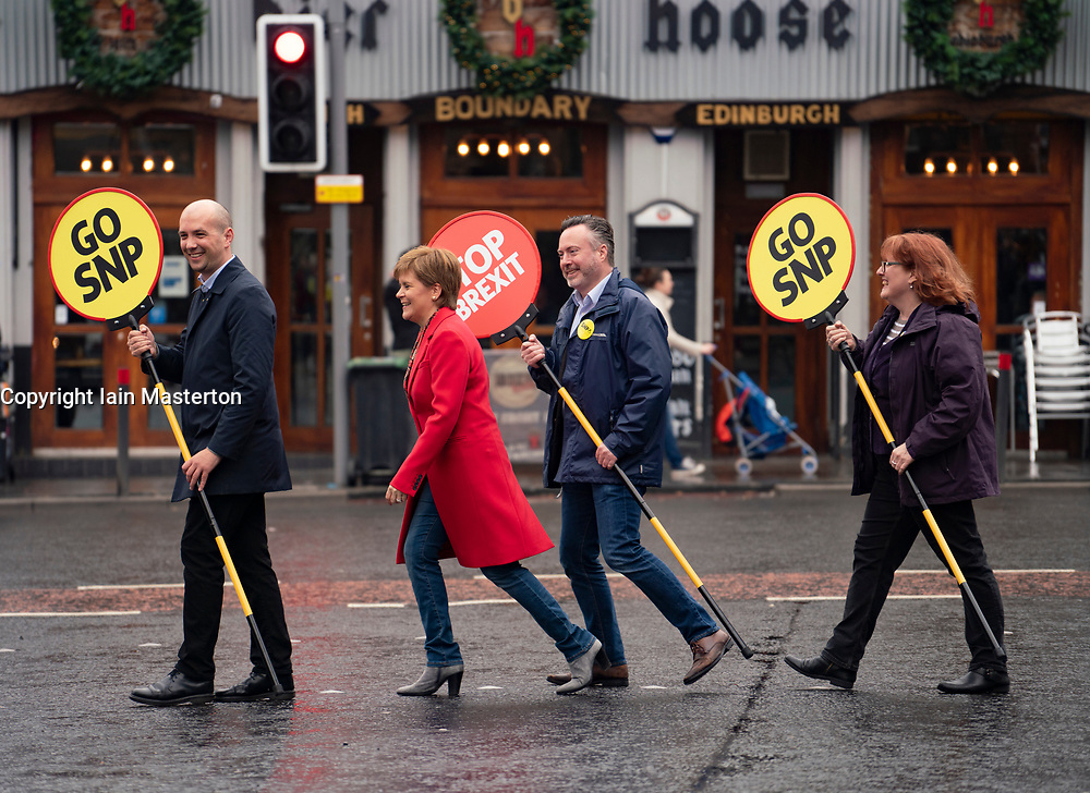 """Edinburgh, Scotland, UK. 18 May 2019. Scotland's First Minister Nicola Sturgeon campaigns alongside lead SNP European candidate Alyn Smith on Leith Walk in Edinburgh. Carrying signs with """"Stop Brexit"""" and """"Go SNP"""" she used a pedestrian crossing at Pilrig Church"""