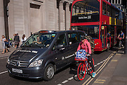 A cyclist in pink pedals gingerly past a Visa-sponsored taxi caught in traffic outside the Bank of England, in the City of London, England UK.