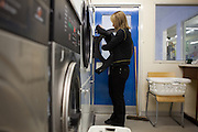 A prisoner washing her clothes in the laundry room. HMP Send, closed female prison. Ripley, Surrey.