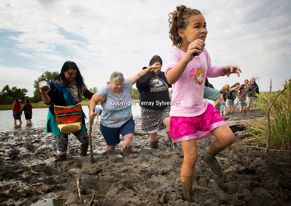 Isabella Flannery of Kansas City, Missouri, picks her way through deep mud after praying with her mother and other women near the route of the Dakota Access oil pipeline and the confluence of the Cannonball and Missouri rivers on August 29, 2016. Cannon Ball, North Dakota, United States.