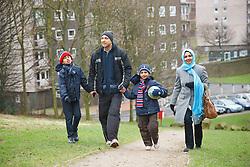 Asian family walking near tower blocks.