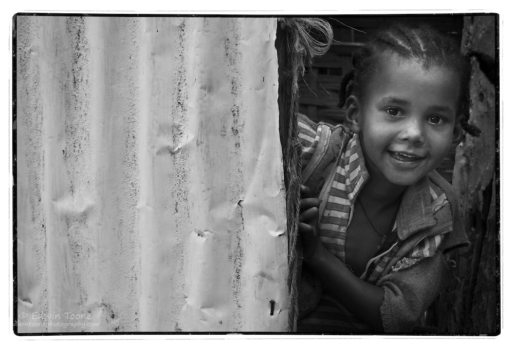 A young Ethiopian girl hides from the camera behind a fence.
