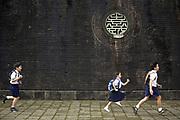 School children run past the walls of The Citadel, Hue, Vietnam.