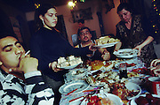 Orthodox Christmas Belgrade. serbia. Midday 7th January.<br />Dzavid Berisa 39yrs with wife Slobodanka (RHS) and daughter Nazmya. Gazmen, brother of Dzavid, smokes cigarette.<br /><br />Food-Pig meat. Sarma - cabbage wrapped sausage meat rolls. Cesnica - a christmas bread with a piece of money inside - the one who finds it will have a prosperous year. Salad, chicken noodle soup. Fruit and nuts and tangerines, dried figs and prunes all traditional. Biscuits - wafers with chocolate.