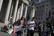 As a woman carries her copy of the Evening Standard newspaper, a muscular young man checks messages below the classical architecture of Royal Exchange and the WW1 war memorial at Bank Triangle, on 10th May 2017, in the City of London, England.
