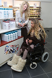 Carer and young woman with Cerebral Palsy shopping choosing shampoo,