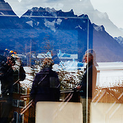 Hikers, mountains and icebergs reflected in hostera window glass at Lago Grey in the Torres del Paine national Park, Patagonia, Chile.