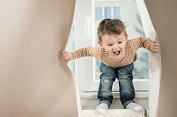 Boy playing with curtain
