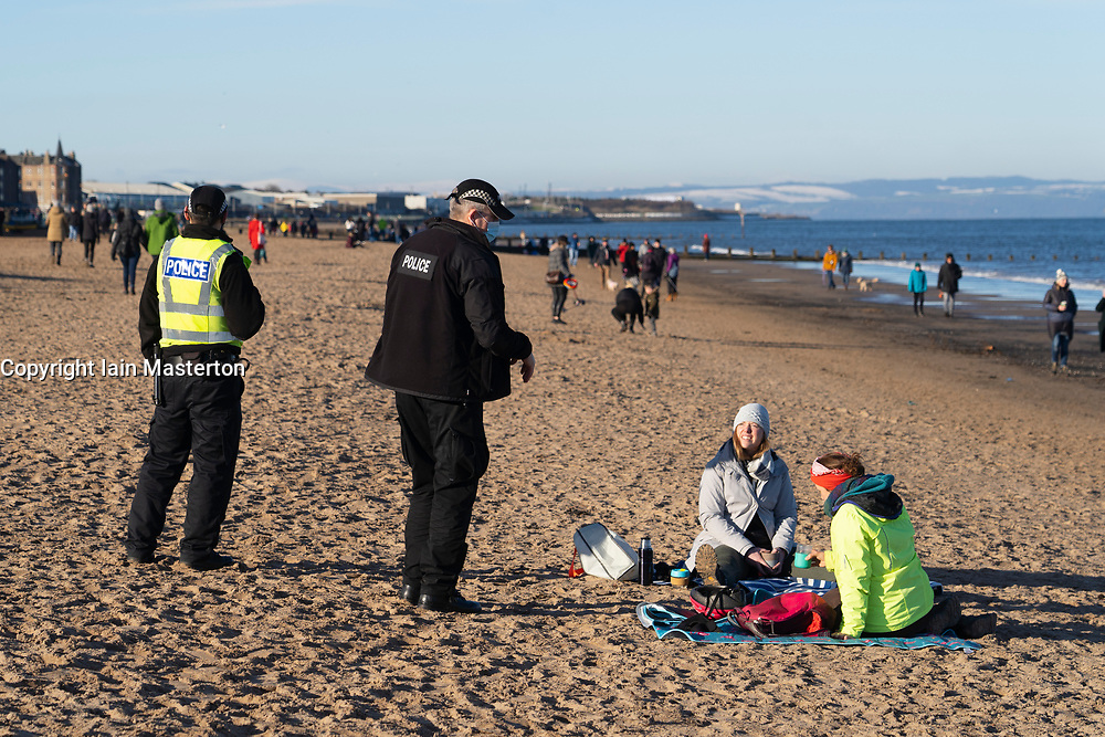 Portobello, Scotland, UK. 24 January 2020. Large numbers of members of the public at Portobello beach and promenade on sunny Sunday afternoon during lockdown. While most people observed social distancing groups of people formed at some of the cafes offering takeaway food and drinks. Police patrols spoke to public sitting down and in groups at cafes to ask them to move on. Pic; Police ask two members of the public not to sit on the beach.  Iain Masterton/Alamy Live News