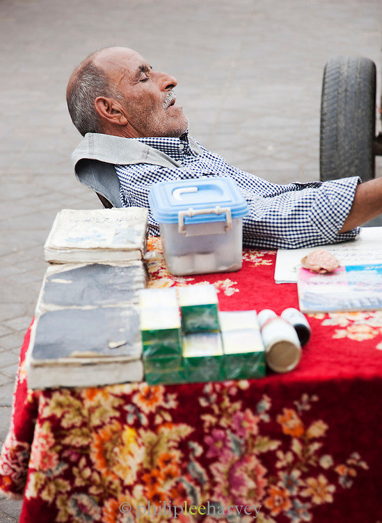 A man asleep at his stall in the Djemaa el Fna in the medina of Marrakech, Morocco