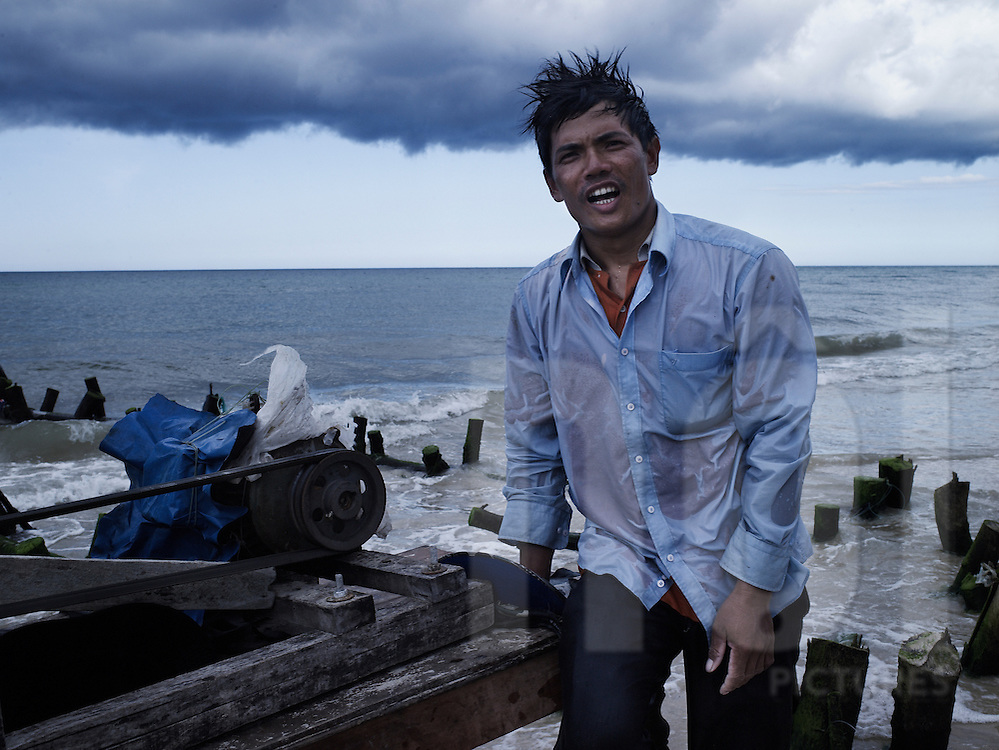 A Vietnamese man in soaking wet clothes aggressively looks towards the camera, Dong Hoi, Quang Binh Province, Vietnam, Southeast Asia