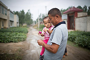 A man carries his grand-daughter down a street at a rural village near Fuyang, Anhui Province,  China on 28 August  2013.  As able-bodied adults seek work in cities in hopes of better income, more and more villages in China are inhabited mostly by the elderly and children.
