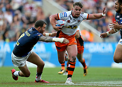 Castleford Tigers' Adam Milner is tackled by Leeds Rhino's Adam Cuthbertson during the Betfred Super League, Magic Weekend match at St James' Park, Newcastle.