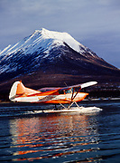 Howard Bowman's Stinson Voyager 108 with a PDX Conversion taxiing on Hardenburg Bay of Lake Clark, Tanalian Mountain beyond, Lake Clark National Park and Preserve, Alaska.