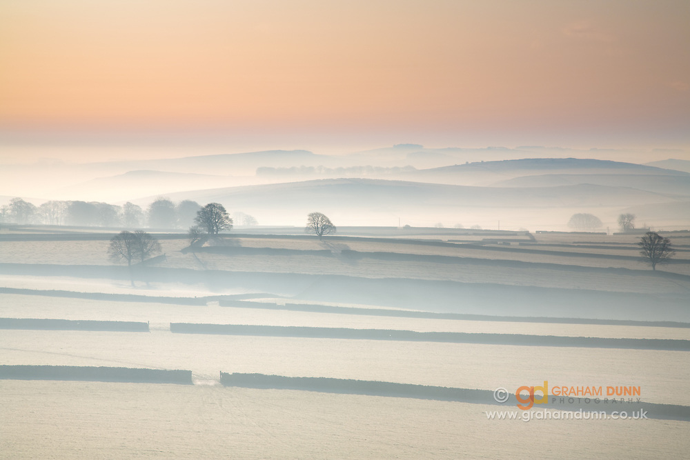 A frosty dawn in the Upper Dove Valley, Peak District. Frosty fields glow in the morning light. A wintery scene of fields, drystone walls, trees and White Peak undulations. Captured from High Wheeldon. England, UK